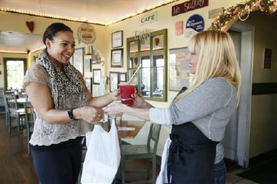Betty Fraser, the owner of Los Angeles restaurant Grub, right, delivers an online order to customer Chantel Mines on Monday Nov. 11, 2013. Fraser's restaurant Grub, has joined the services of an online food ordering company GrubHub, which takes about 15 percent of each order. Photo: AP / AP