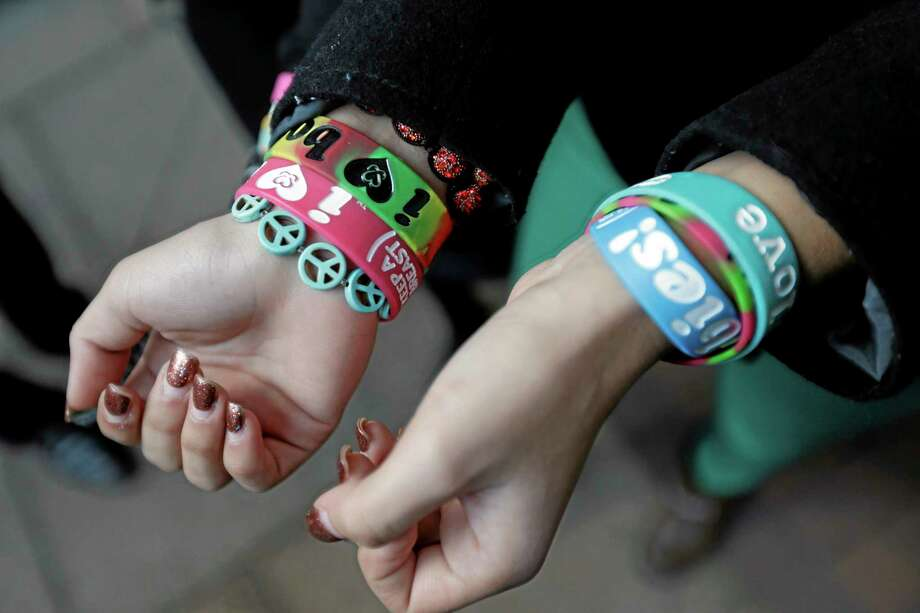 "FILE - In this Feb. 20, 2013 file photo, Easton Area School District students Brianna Hawk, 15, left, and Kayla Martinez, 14, display their bracelets for photographers outside the U.S. Courthouse in Philadelphia. A federal appeals court ruled Monday, Aug. 5, 2013 that a Pennsylvania school district cannot ban ""I (heart) Boobies!"" bracelets, rejecting the district's claim that the slogan — designed to promote breast cancer awareness among young people — is lewd. The ruling is a victory for Hawk and Martinez, who challenged the school rule in 2010 with help from the American Civil Liberties Union. Easton is one of several school districts around the country to ban the bracelets, which are distributed by the nonprofit Keep A Breast Foundation of Carlsbad, Calif. (AP Photo/Matt Rourke, File) Photo: AP / AP"