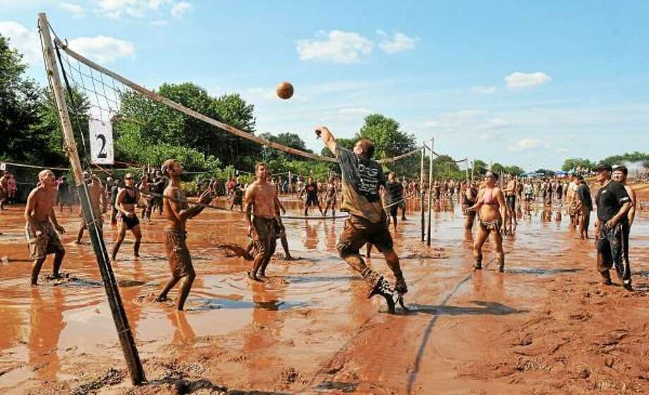 Two hundred and sixteen teams with names like Muddy Mayhem and Captain Mud infiltrated 24 courts at Zoar's Pond at the annual 27th Mud Volleyball Tournament sponsored by the Epilepsy Foundation of Connecticut on Randolph Road in Middletown Saturday afternoon. Over $65,000 was raised for the Epilepsy Foundation. (Catherine Avalone - The Middletown Press) / TheMiddletownPress