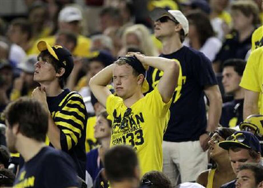 Michigan fans in the stands react to a play during the first half of an NCAA college football game against the Alabama at Cowboys Stadium in Arlington, Texas, Saturday, Sept. 1, 2012. Photo: AP / AP