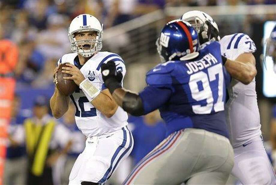 Indianapolis Colts quarterback Andrew Luck (12) looks to pas as New York Giants' Linval Joseph (97) rushes him during the first half of an NFL preseason football game Sunday, Aug. 18, 2013, in East Rutherford, N.J. (AP Photo/Kathy Willens) Photo: AP / AP