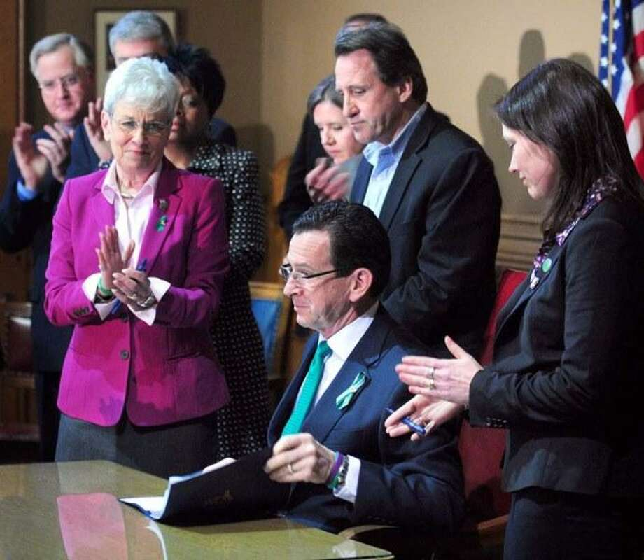 Lt. Governor Nancy Wyman (left), Neil Heslin (top center) and Nicole Hockley (right) applaud as Governor Dannel Malloy (center bottom) completes the signing the Gun Violence Prevention and Child Safety Act at the Capitol in Hartford on 4/4/2013. Photo by Arnold Gold/New Haven Register