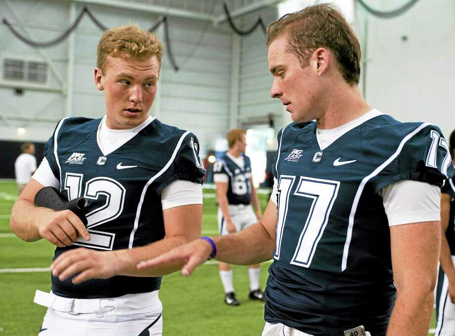 UConn quarterback Casey Cochran, left, was named the Huskies' new starting quarterback on Tuesday. At right is former UConn QB Blaise Driscoll. Photo: Jessica Hill — The Associated Press  / A2012