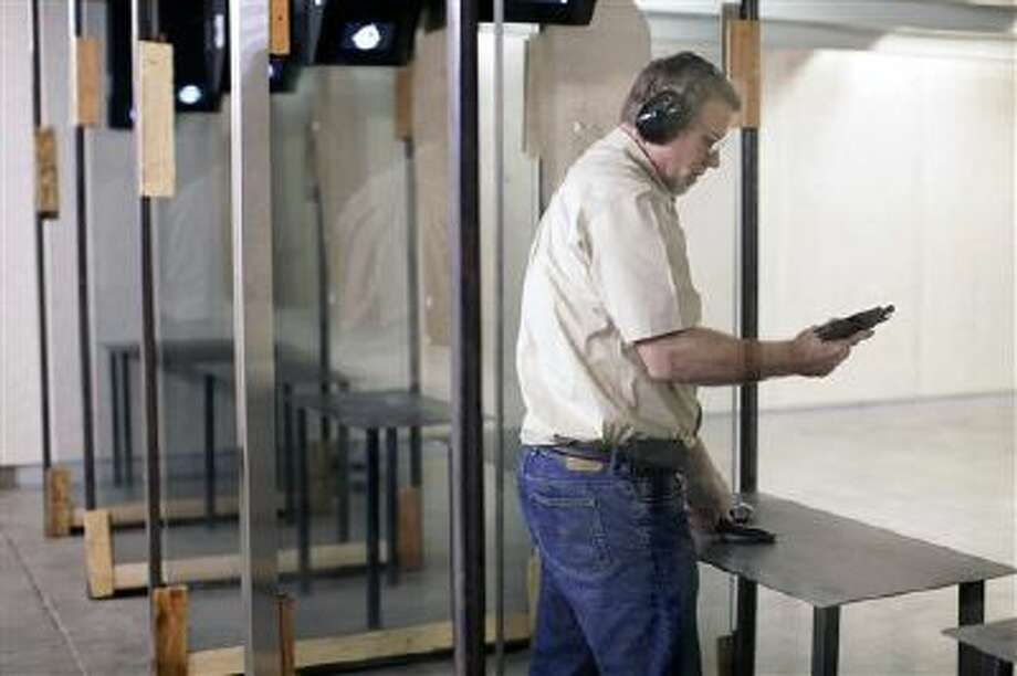 Richard Folsland reloads a Smith & Wesson firearm while using the Smoking Gun Range & Training Center in Box Elder, S.D. Photo: AP / Rapid City Journal