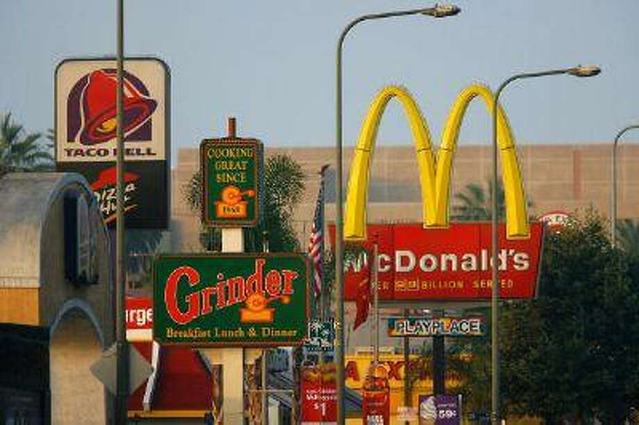 Fast-food restaurants signs line a street July 24, 2008 in the South Los Angeles area of Los Angeles, Calif. Photo: Getty Images / 2008 Getty Images