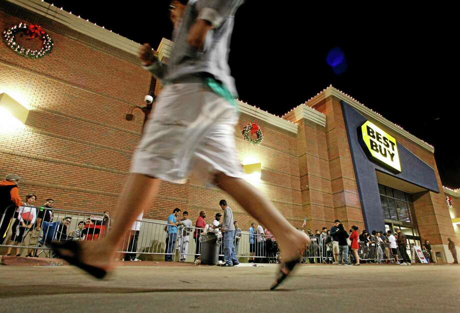 FILE - In this Thursday, Nov. 22, 2012, file photo, shoppers stand in line outside a Best Buy department store before the store's opening at midnight. Thanksgiving is slowly becoming just another shopping day as at least a dozen major retailers are planing to open Thursday, Nov. 28, 2013. (AP Photo/Tony Gutierrez, File) Photo: AP / AP