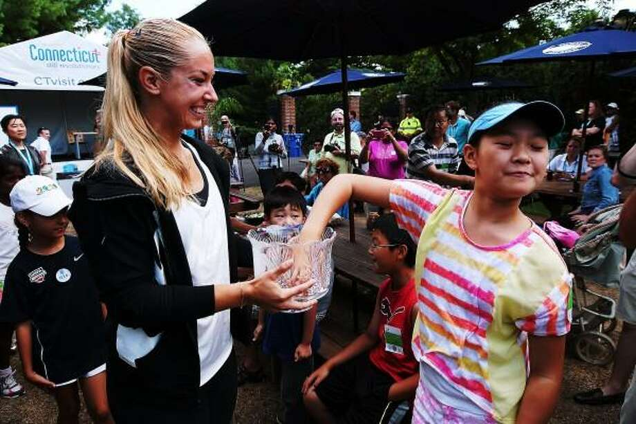Pro Sabine Lisicki gets a pick from Sophia Zhang,11, of Trumbull during the the Draw ceremony at the New Haven Open at Yale. Photo by Peter Casolino - New Haven Register