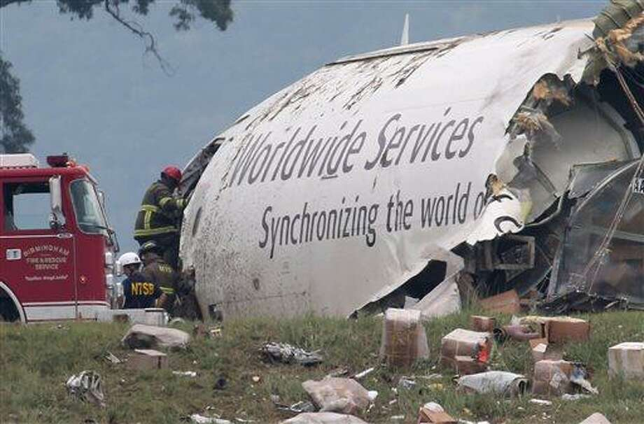 Investigators work near a section of debris of a UPS Airbus A300 cargo plane after it crashed on approach at Birmingham-Shuttlesworth International Airport this morning Wednesday Aug. 14,  2013 in Birmingham, Ala. The two pilots aboard the aircraft were killed.  (AP Photo/Hal Yeager) Photo: AP / FR170776 AP
