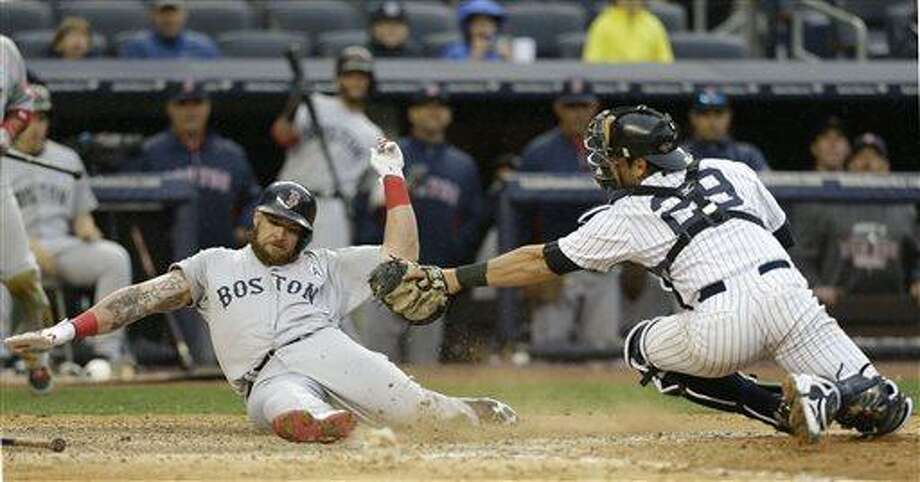 Boston Red Sox Jonny Gomes, left, scores on  a ninth-inning error by New York Yankees second baseman Robinson Cano (not shown) in an opening day baseball game  at Yankee Stadium in New York, Monday, April 1, 2013.  (AP Photo/Kathy Willens) Photo: AP / AP
