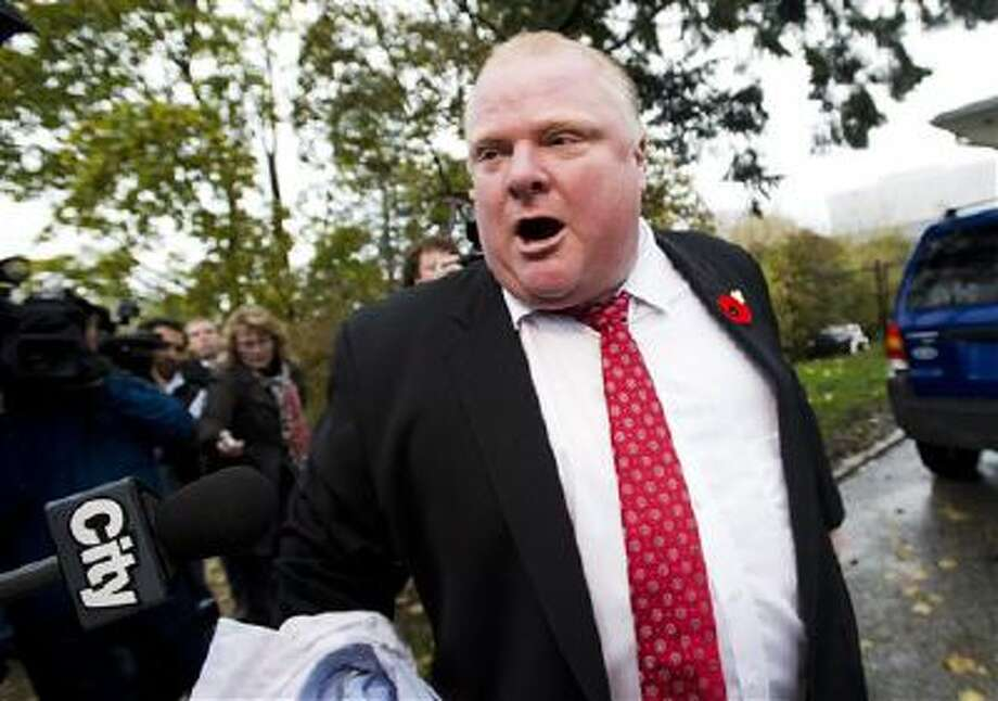 "Toronto Mayor Rob Ford tells to the media to get off his property as he leaves his home in Toronto. The embattled mayor last Tuesday said he smoked crack ""probably a year ago"" during a ""drunken stupor."" Photo: AP / The Canadian Press"