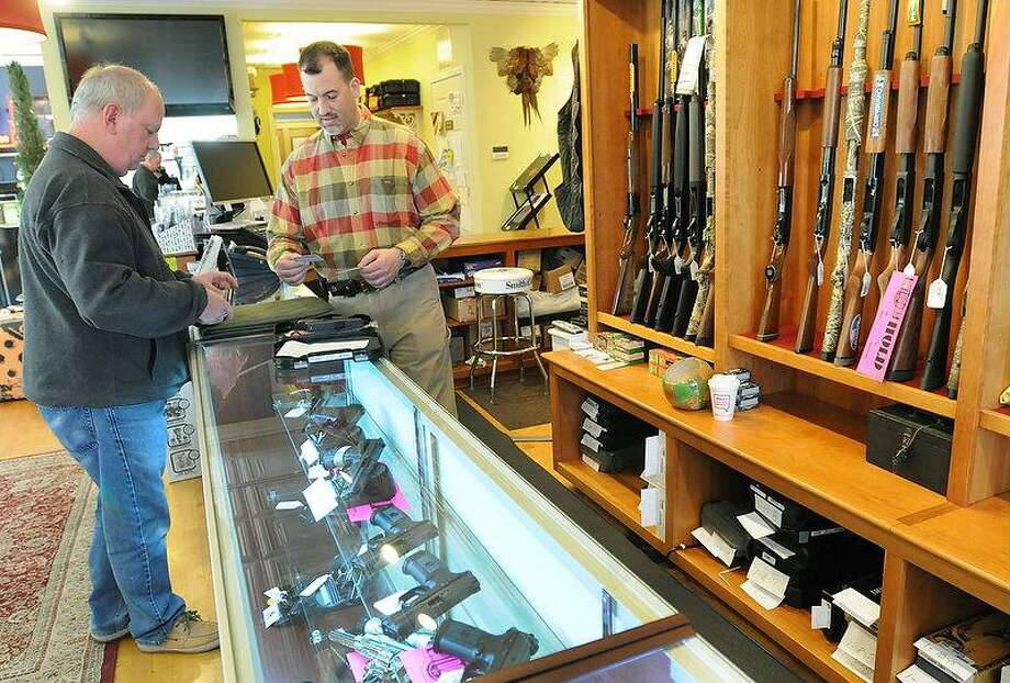 Thomas Powers of Branford, left, shows his pistol permit to Mike Higgins, co-owner of TGS Outdoors on Main Street in Branford as they start the required Federal and State of Connecticut paperwork before he purchases a handgun there Tuesday. Peter Hvizdak/New Haven Register Photo: New Haven Register / ©Peter Hvizdak /  New Haven Register