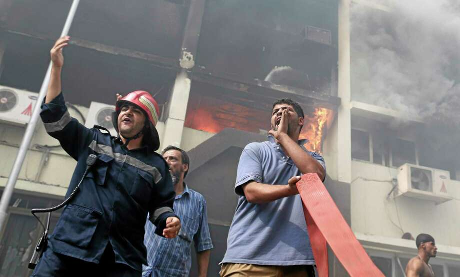 Egyptian firefighters battle flames at the Giza governorate buildings that were stormed and torched by angry supporters of Egypt's ousted president, Cairo, Egypt, Thursday, Aug. 15, 2013. Egypt faced a new phase of uncertainty on Thursday after the bloodiest day since its Arab Spring began, with hundreds of people reported killed and thousands injured as police smashed two protest camps of supporters of the deposed Islamist president. Wednesday's raids touched off day-long street violence that prompted the military-backed interim leaders to impose a state of emergency and curfew, and drew widespread condemnation from the Muslim world and the West, including the United States. (AP Photo/Hassan Ammar) Photo: AP / AP