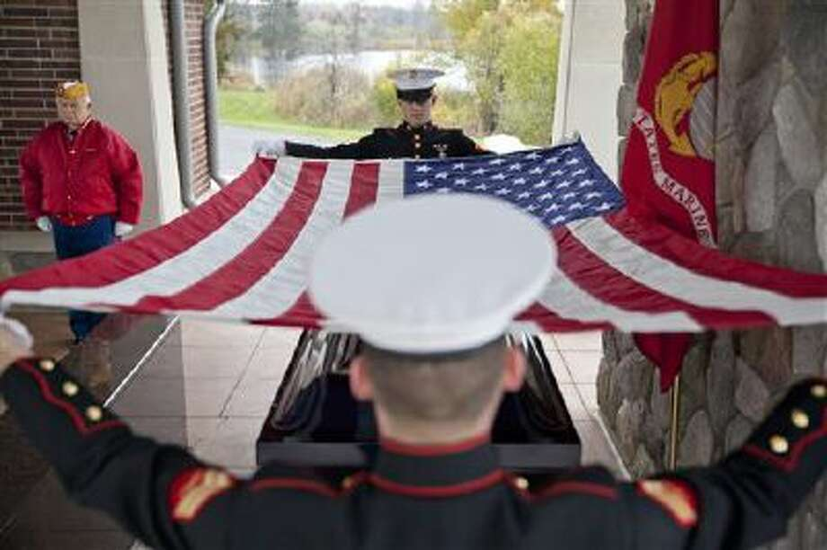 Marines fold an American Flag over a casket on Nov. 5 at Great Lakes National Cemetery in Holly, Mich. The cemetery is staffed year-round by veterans who dig graves and bury the caskets of their fellow servicemen. Photo: AP / The Flint Journal