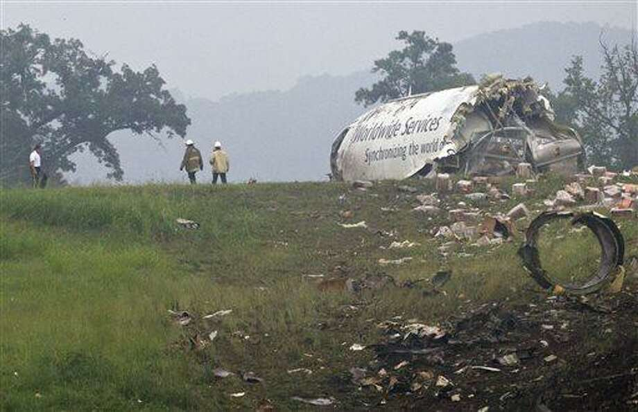 Fire crews investigate where a UPS cargo plane lies on a hill at Birmingham-Shuttlesworth International Airport after crashing on approach, Wednesday, Aug. 14,  2013, in Birmingham, Ala. Toni Herrera-Bast, a spokeswoman for Birmingham's airport authority, says there are no homes in the immediate area of the crash. (AP Photo/Butch Dill) Photo: ASSOCIATED PRESS / ASSOCIATED PRESS2013