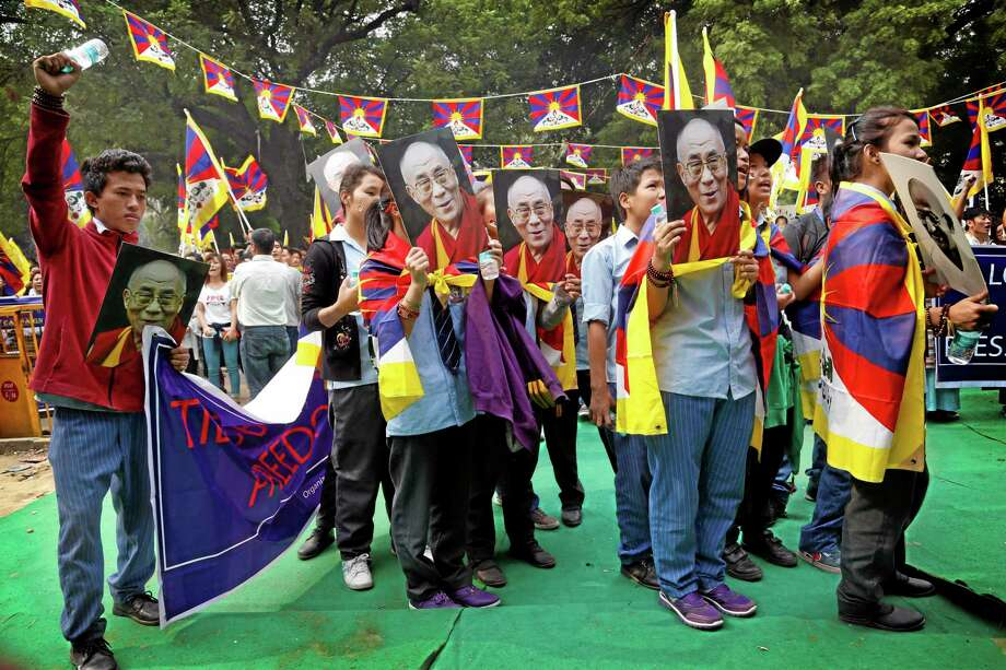 Tibetans hold up portraits of spiritual leader the Dalai Lama and Indian freedom fighter Mahatma Gandhi during a protest rally in New Delhi, India, Wednesday, Nov. 6, 2013. The rally was held to seek the attention of the international community towards the plight of Tibetans in Tibet and for the release of Tibetan political prisoners in China, among others, according to a press release. (AP Photo /Manish Swarup) Photo: AP / AP