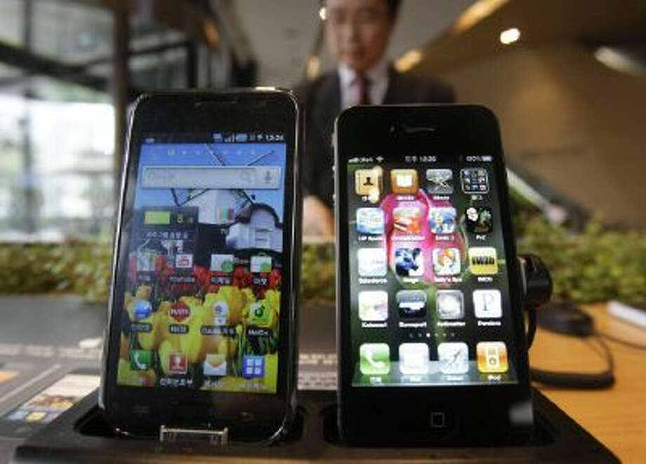 Samsung Electronics' Galaxy S, left, and Apple's iPhone 4 are displayed at the headquarters of South Korean mobile carrier KT in Seoul, South Korea.