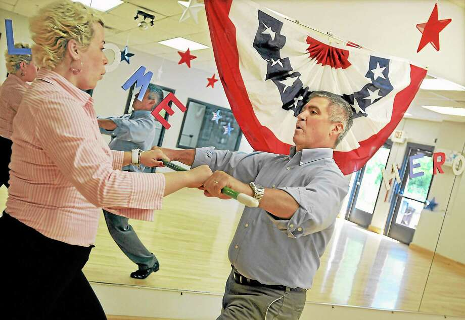 "Professional dancer Marlena Chabowska, an instructor at Fred Astaire Dance Studio in Middletown, uses a broom to help Jim Lucas with balance, posture and poise while learning to dance the waltz Monday afternoon. Lucas, a retired command chief master sergeant with the U.S. Air Force, will compete in ""Dancing With Our Heroes,"" a gala honoring the U.S. Military, which will benefit The Friends of Fisher House Connecticut. Catherine Avalone - The Middletown Press Photo: Journal Register Co. / TheMiddletownPress"