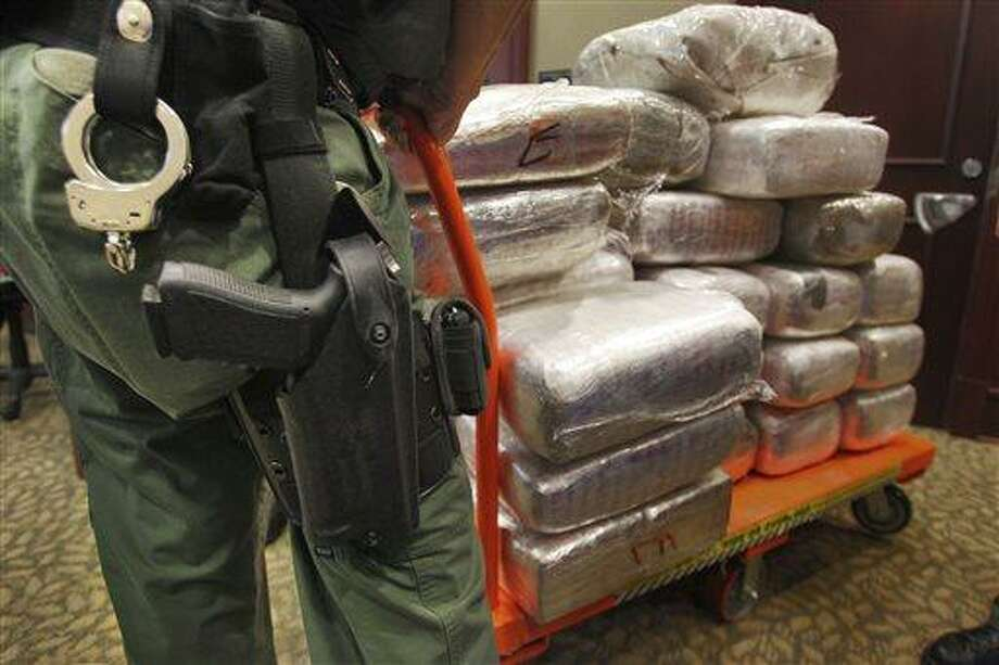 In this Nov. 4, 2010 file photo, bales of marijuana are wheeled out at a news conference in Jonesboro, Ga. Forty-five people were arrested 45 people along with cash, guns and more than two tons of drugs as part of an investigation by federal and local law enforcement into the Atlanta-area U.S. distribution hub of Mexico's La Familia drug cartel. AP Photo/Atlanta Journal-Constitution, John Spink Photo: AP / Atlanta Journal-Constitution