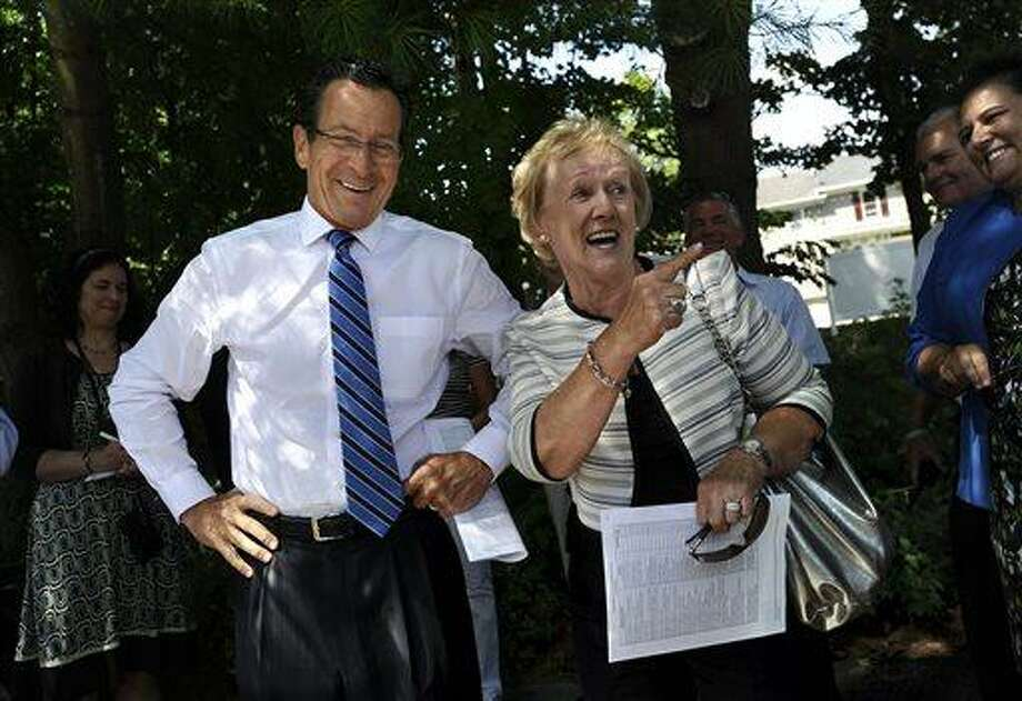 Connecticut Gov. Dannel P. Malloy, left, and Newtown First Selectwoman Patricia Llodra talk before a tour the downtown business district of Sandy Hook in Newtown, Conn., Wednesday, July 31, 2013.  Malloy is visiting to meet with business owners and talk about economic recovery after the December elementary school shooting that killed 20 students and six adults. (AP Photo/Jessica Hill) Photo: AP / FR125654 AP