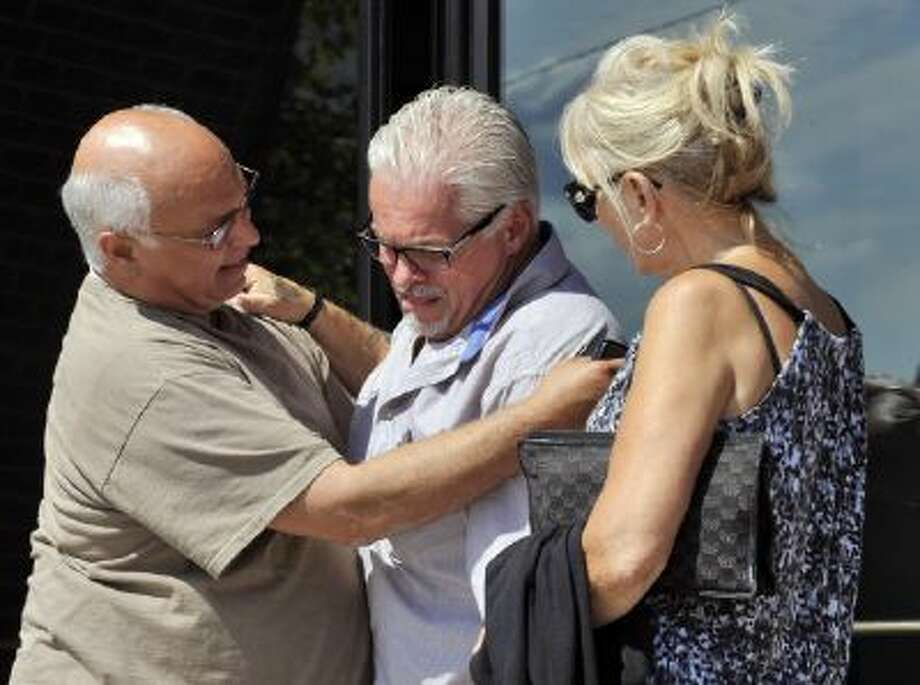 """In this photo made Aug. 12, 2013, Steven Davis, brother of slain Debra Davis, center, is comforted by Skip Marcella, left, after speaking outside federal court in Boston where a jury found James """"Whitey"""" Bulger guilty on several counts of murder, racketeering and conspiracy."""