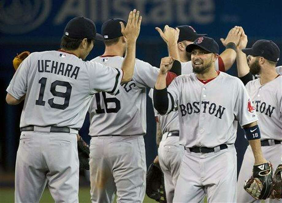 Boston Red Sox out fielder Shane Victorino, center, celebrates with teammates after hitting the winning run to defeat the Toronto Blue Jays during the eleventh inning of a baseball game in Toronto on Tuesday, August 13, 2013. (AP Photo/The Canadian Press, Nathan Denette) Photo: AP / The Canadian Press