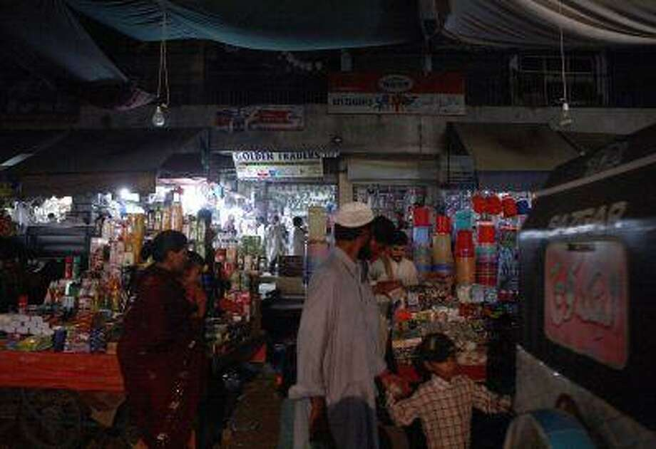 Shoppers walk past a vendor using electricity from a generator to light his shop during a blackout in Karachi. Almost 10 million Pakistanis work overseas, with the amount of money they've sent home doubling in the four years through June to a record $13 billion.