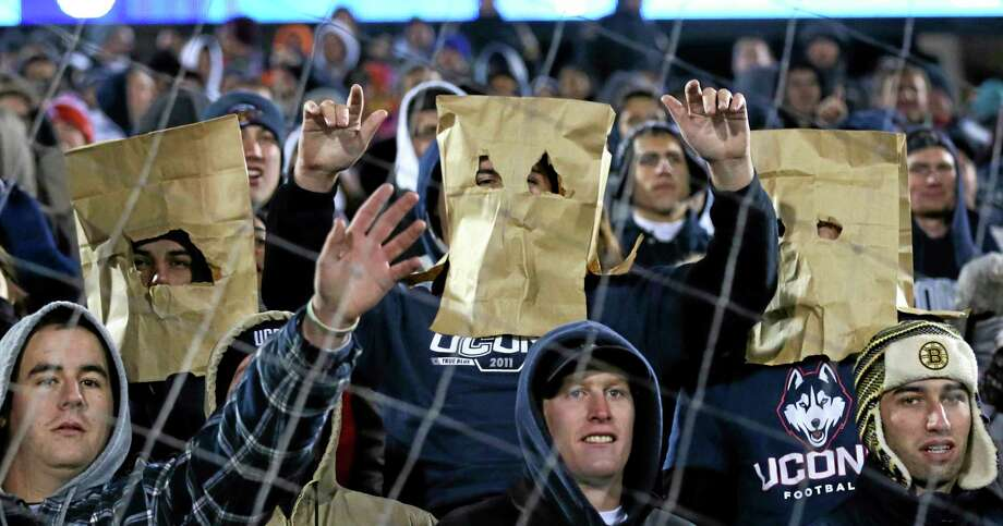 UConn fans wear paper bags over their heads during Friday night's 31-10 loss to No. 20 Louisville at Rentschler Field in East Hartford. Photo: Charles Krupa — The Associated Press  / AP