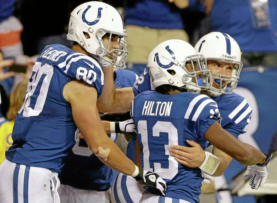 Colts quarterback Andrew Luck celebrates his touchdown with tight end Coby Fleener (80) and wide receiver T.Y. Hilton (13) during the Oct. 20 game against the Denver Broncos in Indianapolis. Mike Wollschlager has the Colts remaining in the top spot of the Week 10 Register NFL Rankings after they rallied to avoid an upset at the hands of the Texans last week. Photo: Michael Conroy — The Associated Press  / AP