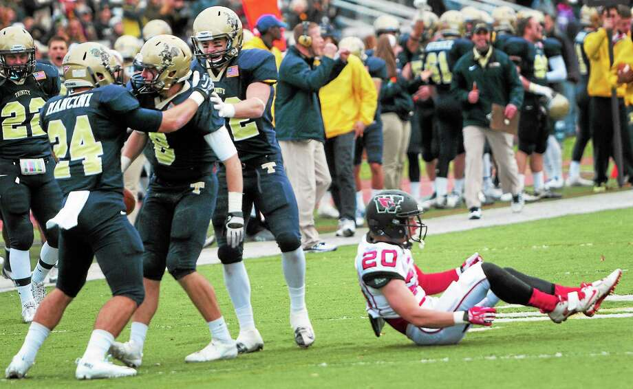 Trinity teammates congratulate strong safety Brendan Bader, third from left, after Bader intercepted a pass intended for Wesleyan's Rob Manning during the first quarter Saturday. Photo: Peter Hvizdak — Register  / ©Peter Hvizdak /  New Haven Register