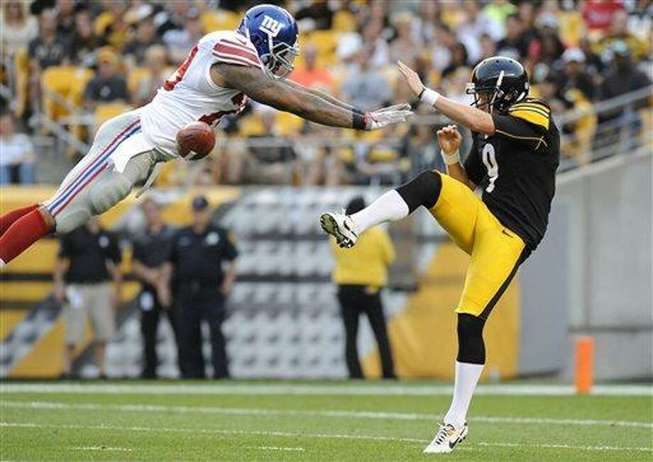 New York Giants' Damontre Moore, left, blocks a punt by Pittsburgh Steelers punter Drew Butler (9) in the first quarter of an NFL preseason football game Saturday, Aug. 10, 2013, in Pittsburgh. (AP Photo/Don Wright) Photo: AP / FR87040 AP