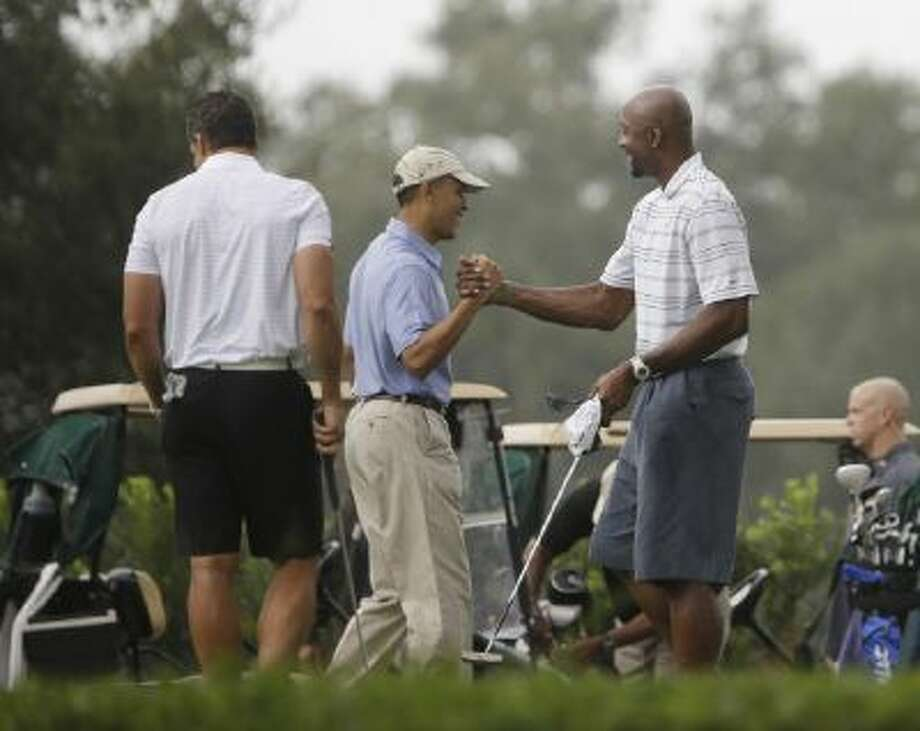 President Barack Obama, center, shakes hands with former NBA basketball player Alonzo Mourning, right, at Grande Oaks golf club, Saturday, Nov. 9, 2013 in Ft. Lauderdale, Fla. Obama traveled to the Miami area yesterday for a series of private Democratic fundraisers and a golf outing today.