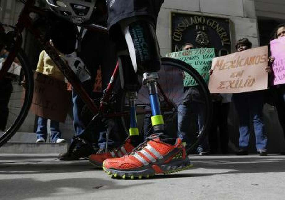 Cyclist Carlos Gutierrez, a double amputee, center, stands with his bike during a stop at the Mexican Consulate, Thursday, Nov. 7, 2013, in San Antonio.