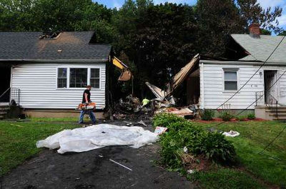 Officials inspect the debris on Saturday, Aug. 10, 2013 after a small plane, piloted by Bill Henningsgaard, crashed into two homes Friday in East Haven, Conn. Four people were killed in the incident. (AP Photo/The New Haven Register, Peter Hvizdak) Photo: AP / The New Haven Register