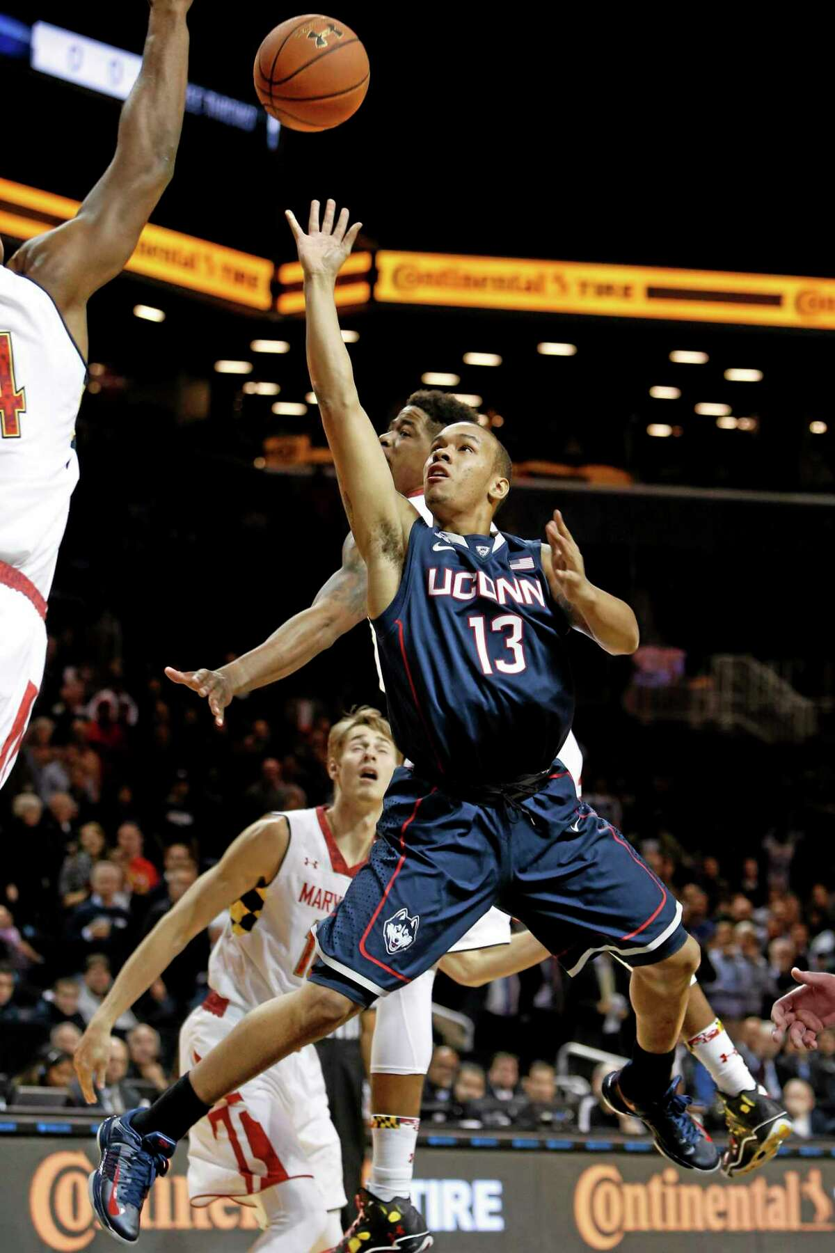 Connecticut's Shabazz Napier (13) shoots against Maryland's Shaquille Cleare, left, during the first half of an NCAA college basketball game Friday, Nov. 8, 2013, in New York. (AP Photo/Jason DeCrow)