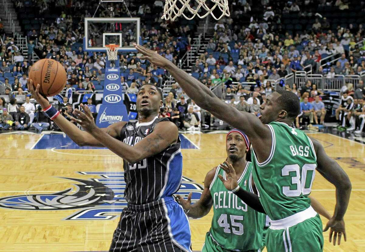 The Magic's E'Twaun Moore, left, tries to shoot over the Boston Celtics' Gerald Wallace (45) and Brandon Bass (30) during the first half of Friday night's game in Orlando, Fla.