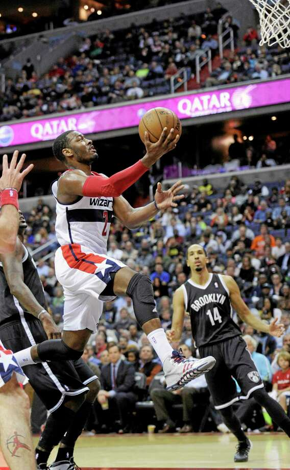 Wizards guard John Wall (2) goes to the basket against Brooklyn Nets guard Shaun Livingston during the second half of Friday night's game in Washington. The Wizards won 112-108 in overtime. Photo: Nick Wass — The Associated Press  / FR67404 AP