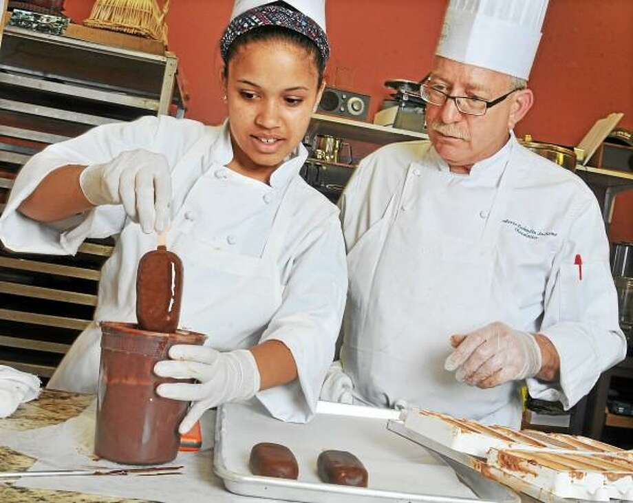 Chocolatier Roberto Lucheme teaches Zahria McDaniel, 14 how to dip the Mighty Moussicles Friday afternoon at Tschudin Chocolates & Confections on Main Street in Middletown. McDaniel, a rising sophomore at Middletown High School is part of the Middlesex Chamber of Commerce Youth at Work program. Catherine Avalone - The Middletown Press / TheMiddletownPress
