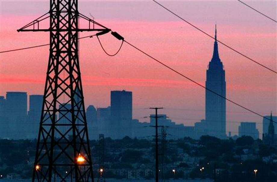 ADVANCE FOR SUNDAY EDITIONS OF AUG. 11 -FILE - In a Friday, Aug. 15, 2003, file photo the Empire State Building towers over the skyline of a  blackout darkened New York City  just before dawn.  Power lines from Jersey City, N.J., are  in foreground. Ten years after a blackout cascading from Ohio affected 50 million people, utilities and analysts say changes made in the aftermath make a similar outage unlikely today, though shifts in where and how power is generated raise new reliability concerns for the U.S. electric grid system. (AP Photo/File, George Widman, File) Photo: AP / AP