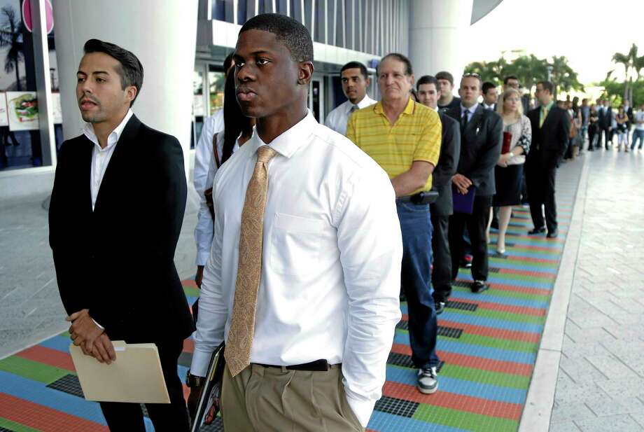 FILE - In this Wednesday, Oct. 23, 2013, file photo, Luis Mendez, 23, left, and Maurice Mike, 23, wait in line at a job fair held by the Miami Marlins, at Marlins Park in Miami. The jobs report for October, due out Friday, could jump by the most in three years.  But the figures will reflect the government's partial shutdown, which coincided with 16 days in October. The trends for the job market will likely reverse themselves in coming months. (AP Photo/Lynne Sladky, FIle) Photo: AP / AP