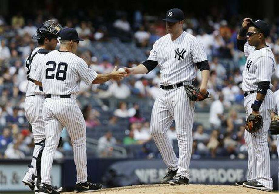New York Yankees starting pitcher Phil Hughes hands the ball to manager Joe Girardi (28) as Robinson Cano (24) looks on during the fifth inning of a baseball game against the Detroit Tigers Saturday, Aug. 10, 2013, in New York. (AP Photo/Frank Franklin II) Photo: AP / AP