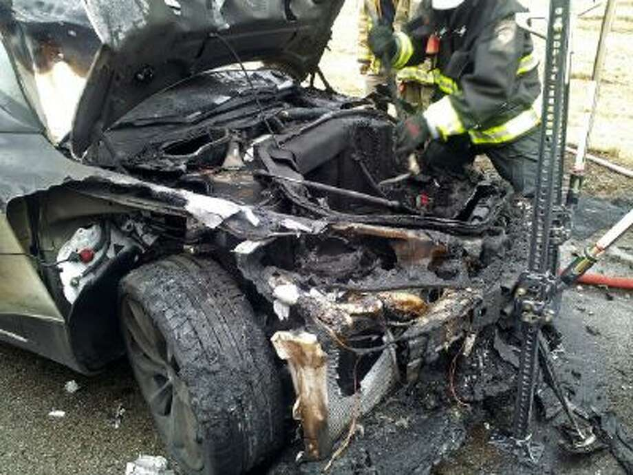 In this Wednesday, Nov. 6, 2013 photo provided by the Tennessee Highway Patrol, emergency workers respond to a fire on a Tesla Model S electric car in Smyrna, Tenn. Spokeswoman Liz Jarvis Shean says Tesla has sent a team to Tennessee to investigate the fire.