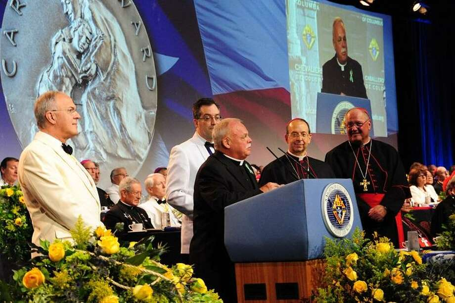 Monsignor Robert Weiss and Grand Knight Timothy Haas of Newton, Conn., accept the inaugural Caritas Awards for exemplary works of charity at the States Dinner of the 131st Knights of Columbus Supreme Convention. The award was presented by Supreme Knight Carl Anderson and Supreme Chaplain Archbishop William E. Lori of Baltimore. Also present was Cardinal Timothy Dolan of New York and nearly 90 bishops and cardinals from around the world. / RUSSELL MCBRIDE