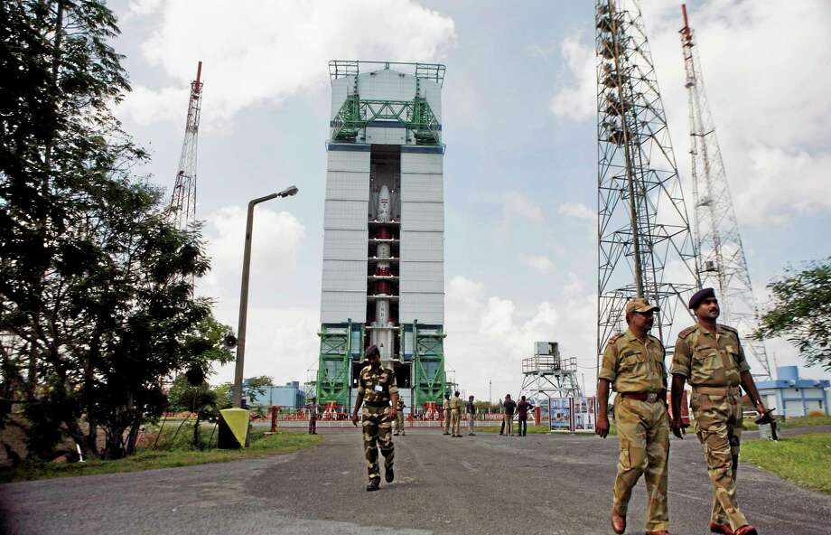 In this Wednesday, Oct. 30, 2013 photo, Central Industrial Security Force (CISF) personnel walk near the Polar Satellite Launch Vehicle (PSLV – C25) at the Satish Dhawan Space Center at Sriharikota, in the southern Indian state of Andhra Pradesh. India is aiming to join the world's deep-space pioneers with a journey to Mars that it hopes will showcase its technological ability to explore the solar system while seeking solutions for everyday problems on Earth. (AP Photo/Arun Sankar K.) Photo: AP / AP