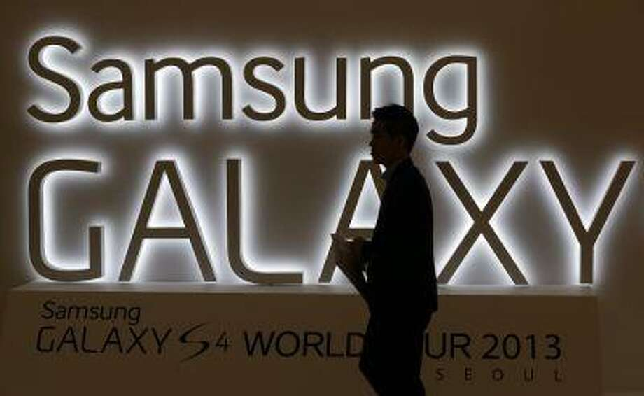 In this photo taken on April 25, 2013, a man walks by a logo of Samsung Electronics Co.'s latest smartphone Galaxy S4 during its unveiling ceremony in Seoul, South Korea. Samsung Electronics Co. has applied for U.S. and South Korean trademarks for a watch that connects to the Internet in the latest sign that consumer technology companies see wearable devices as the future of their business. (AP Photo/Lee Jin-man) Photo: AP / AP
