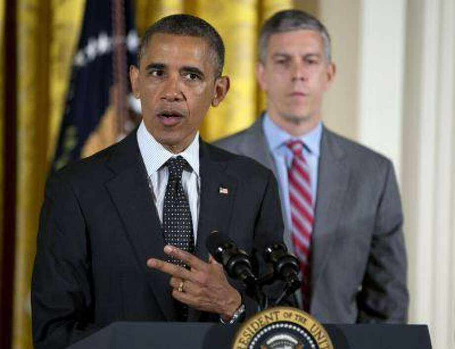 In this June 3, 2013 file photo, Education Secretary Arne Duncan, right, listens as President Barack Obama speaks in the East Room of the White House in Washington. Photo: AP / AP