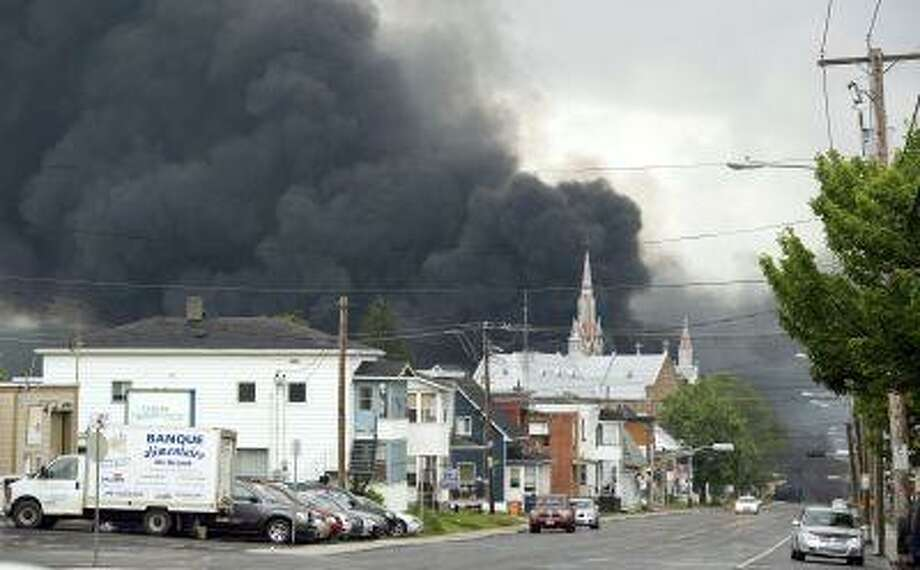 Smoke rises from railway cars that were carrying crude oil after derailing in downtown Lac Megantic, Quebec, Canada, Saturday, July 6, 2013. Photo: ASSOCIATED PRESS / AP2013