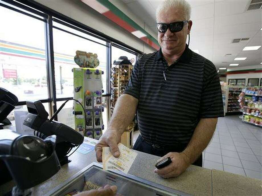 Richard Rennick of Dallas, takes his Powerball and Texas Lotto tickets after making a purchase at a store loacation, Wednesday, Aug. 7, 2013, in Dallas. Sue Dooley, senior drawing manager production coordinator for the Multi-State Lottery Association, said late Wednesday night that three tickets matched all six numbers and would split the $448 million Powerball jackpot. (AP Photo/Tony Gutierrez) Photo: AP / AP
