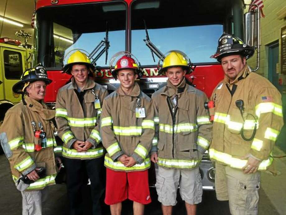New Graduates from the Introduction to the Fire Academy at the Connecticut Fire Academy volunteer at the Durham Volunteer Fire Department. From left, Program Co-Adviser Jenn Kinzeo, graduates Jonathan Cooper, Tyler Crisp, Andrew Conway and Co-Adviser Justin Lonergan. (Mike T. Lyle -- The Middletown Press)