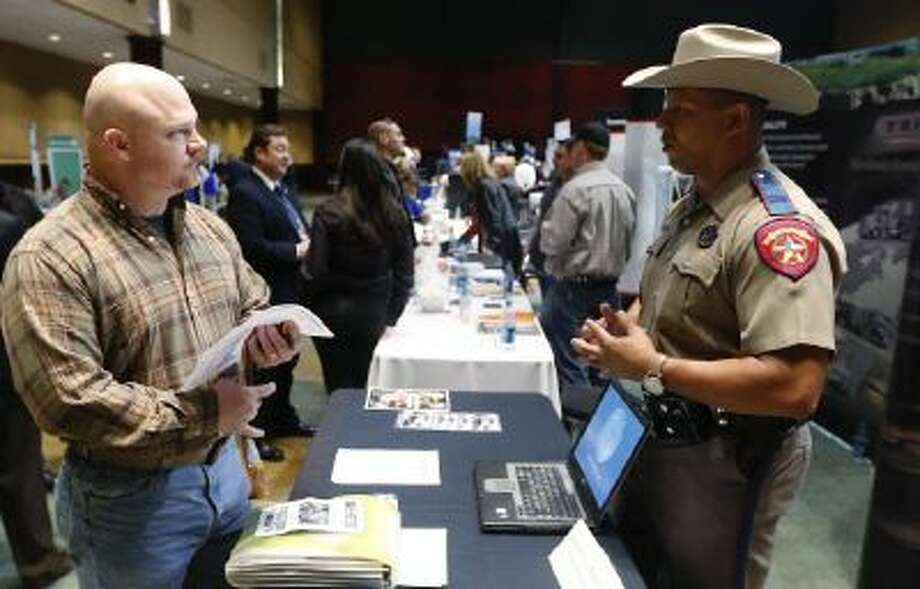 Air Force veteran Brett Culver, left, talks with Texas state trooper Deon Cockrell at a Recruit Military job fair in Oklahoma City. Young veterans have a harder time finding work.