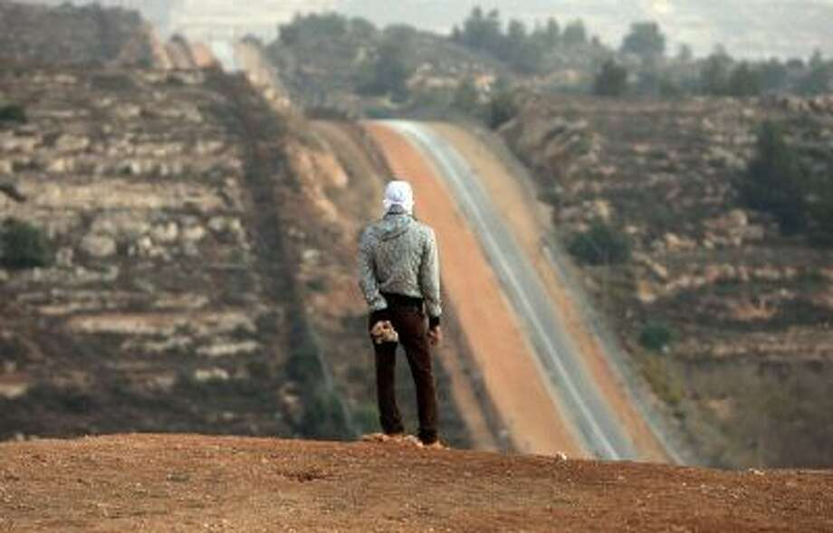 A Palestinian man holds a stone during clashes close to the Israeli military prison of Ofer, near the village of Betunia in the West Bank. Israel's two-state opponents dream of a Greater Israel in which Palestinian areas would be annexed.